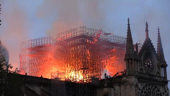 Лестницы прибывших к зданию Нотр-Дама пожарных не достают до пламени - видео