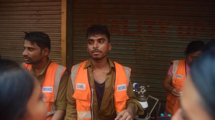 Спасаются по скрученной одежде, прыгают из окон: В Бангладеше горит многоэтажный дом - видео